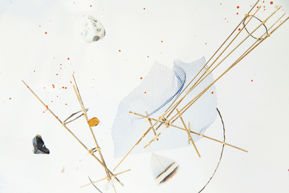 Pierres éloignées, pierres, bois, pigments, tulle, plumes et@ombres sur plexiglas (25 x 90 x 18 cm)